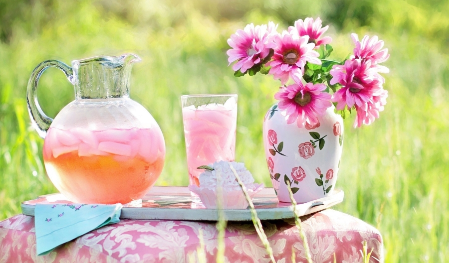 Pink lemonade in a glass jug wiht a vase of pink flowers